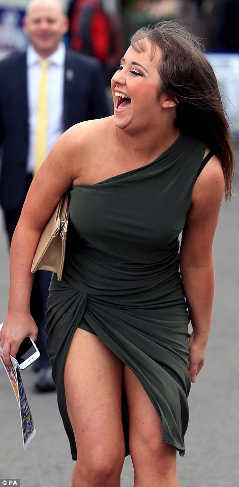 A laughing reveller can't contain her excitement as she arrives in a dark grey dress