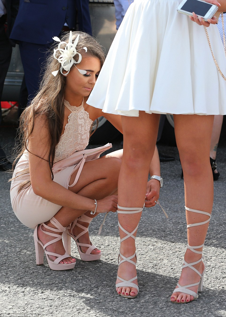 A woman helps her friend do up her gladiator style standards