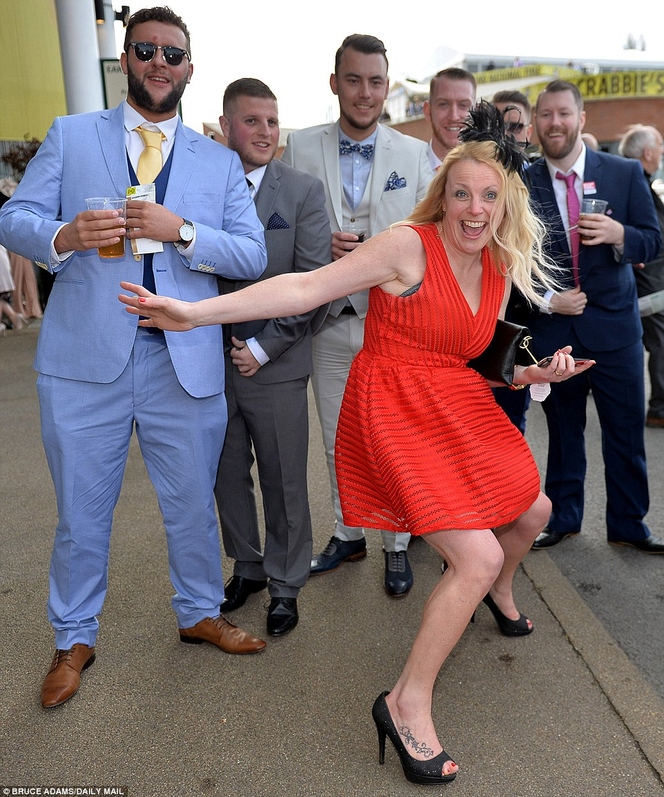 A woman put her less enthusiastic male companions to shame as she threw her arms out and beamed for the camera