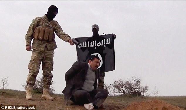 Um funcionário do governo iraquiano que foi encontrado durante uma busca veículo em um posto de controle na província de Anbar, no Iraque, é executado por um lutador ISIS enquanto outro segura uma bandeira no fundo