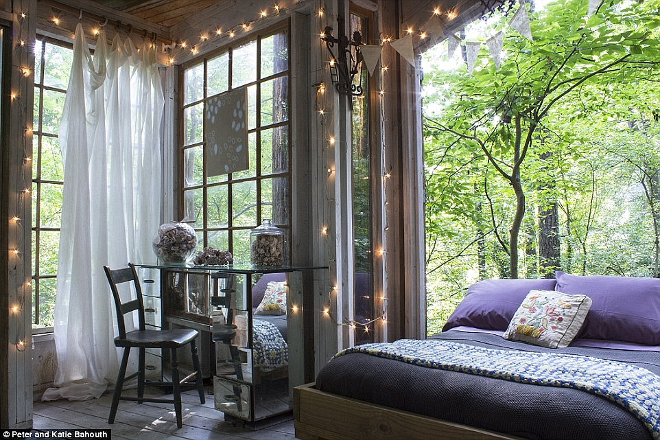 Floor-to-ceiling windows flood the interior with natural light, while pretty fairy lights and swishy curtains add a dash of romance to the scheme