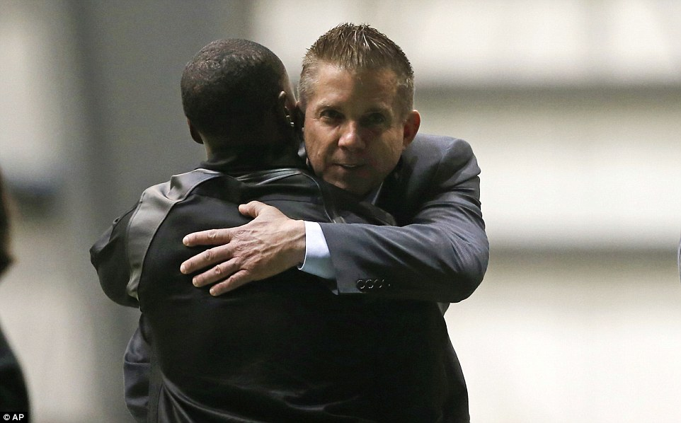 New Orleans Saints head coach Sean Payton (facing the camera), who led Smith to Super Bowl glory in 2009, hugs former running back Darren Sproles during the viewing. The pair played together on the team