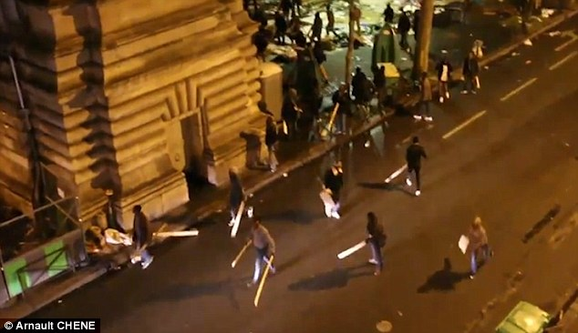 Armed and dangerous: Scores of people armed themselves with planks of wood, metal bars and debris