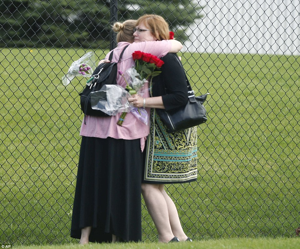 Grief: Two women embrace outside Paisley Park Studios, the home and studio of singer Prince, after his death on Thursday