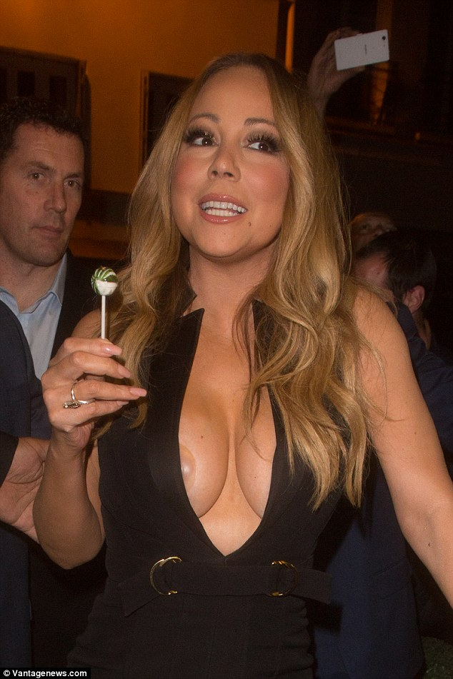 Spilling out: Mariah Carey revealed a little bit more than she bargained for on Thursday night with the star's nipple cover poking out from inside her plunging LBD as she arrived at the VIP Room in Paris