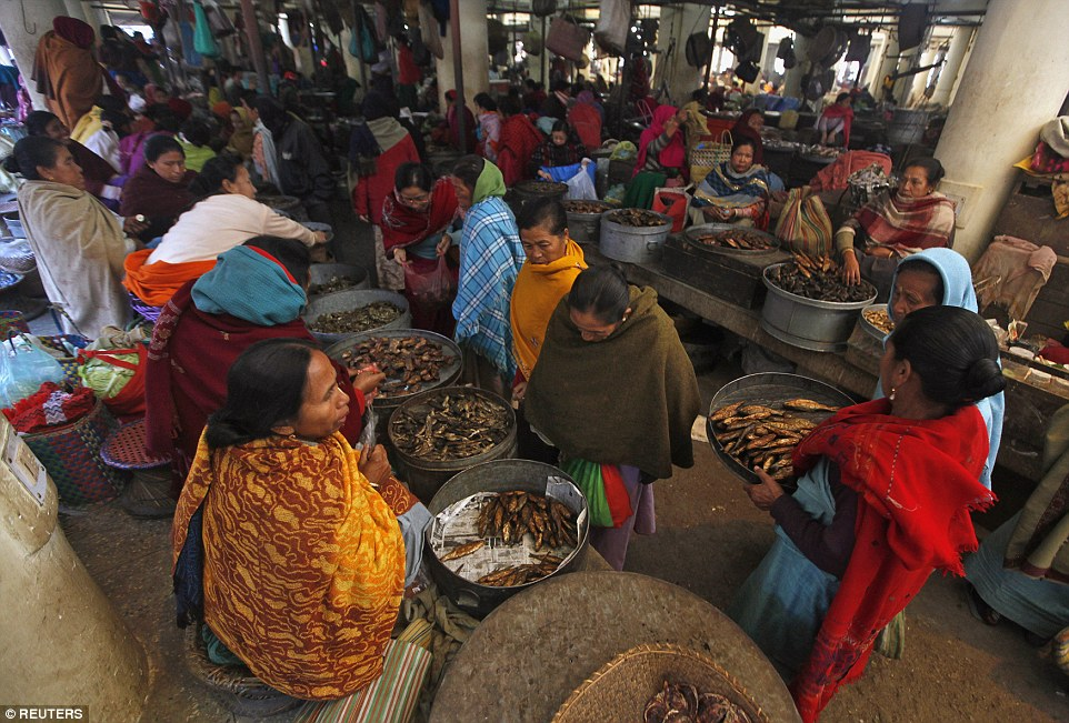 Despite threat of closure over the years, the market is still thriving. Women buy fish at Ima Market (pictured)
