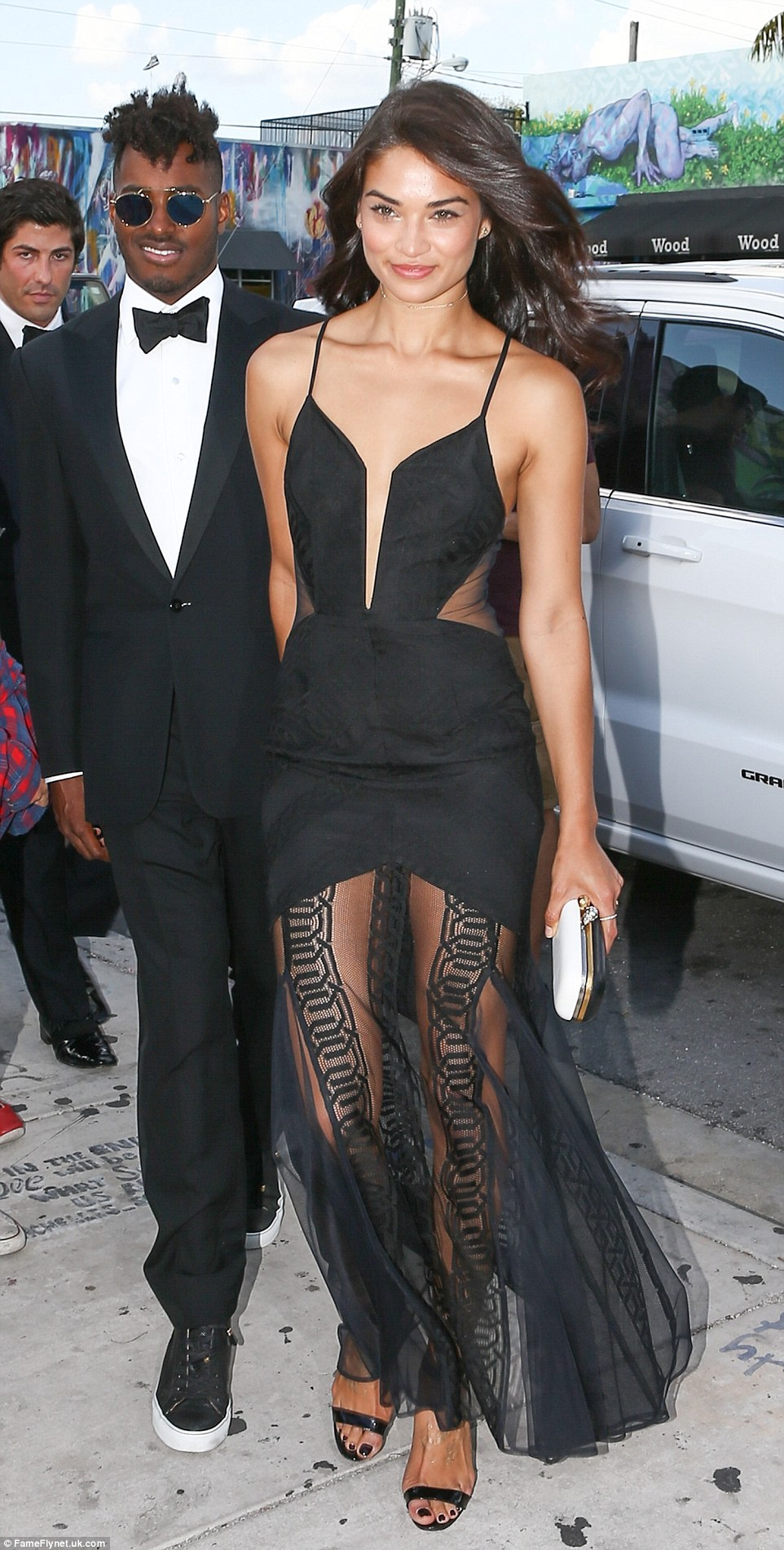 Model Shanina Shaik wore a slashed front black dress with a sheer mesh skirt