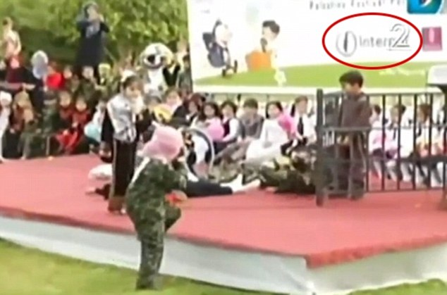 Terror: A boy dressed as a masked terrorist, mounts an 'attack' with a toy gun. The Interpal logo is circled