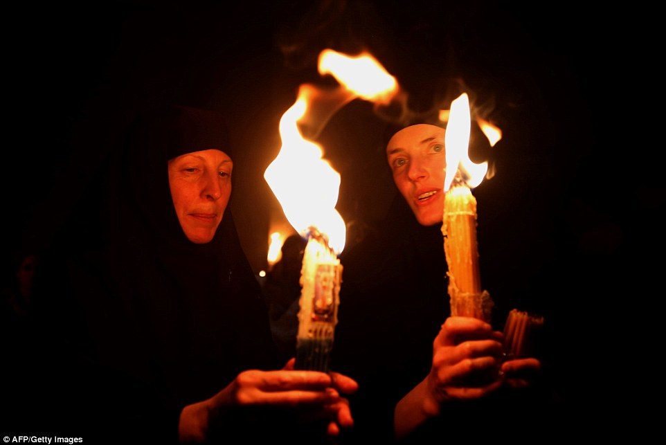 """Russian Orthodox nuns hold candles lit from the """"Holy Fire"""" as thousands gather in the Church of the Holy Sepulchre in Jerusalem"""