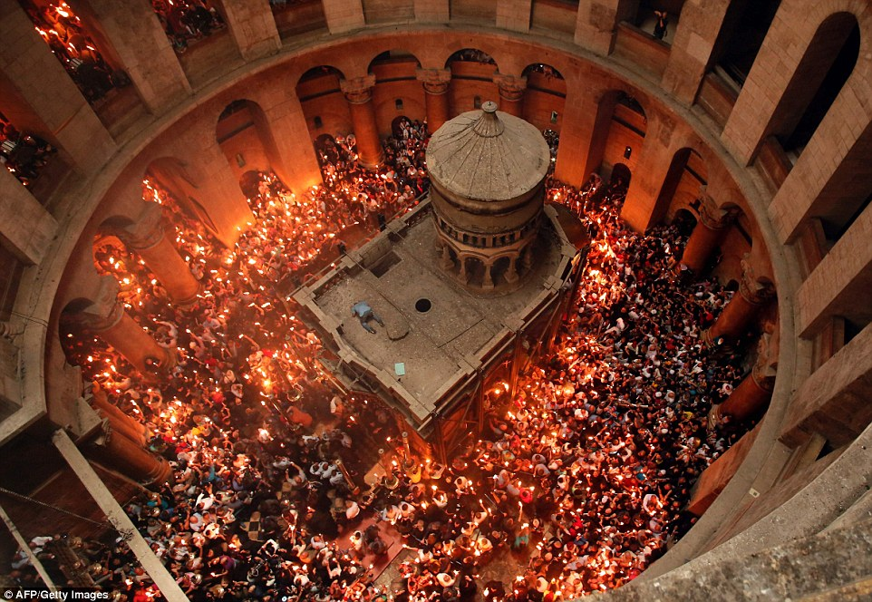 Christian Orthodox worshippers hold up candles lit from the 'Holy Fire' as thousands gather in the Church of the Holy Sepulchre in Jerusalem's Old City