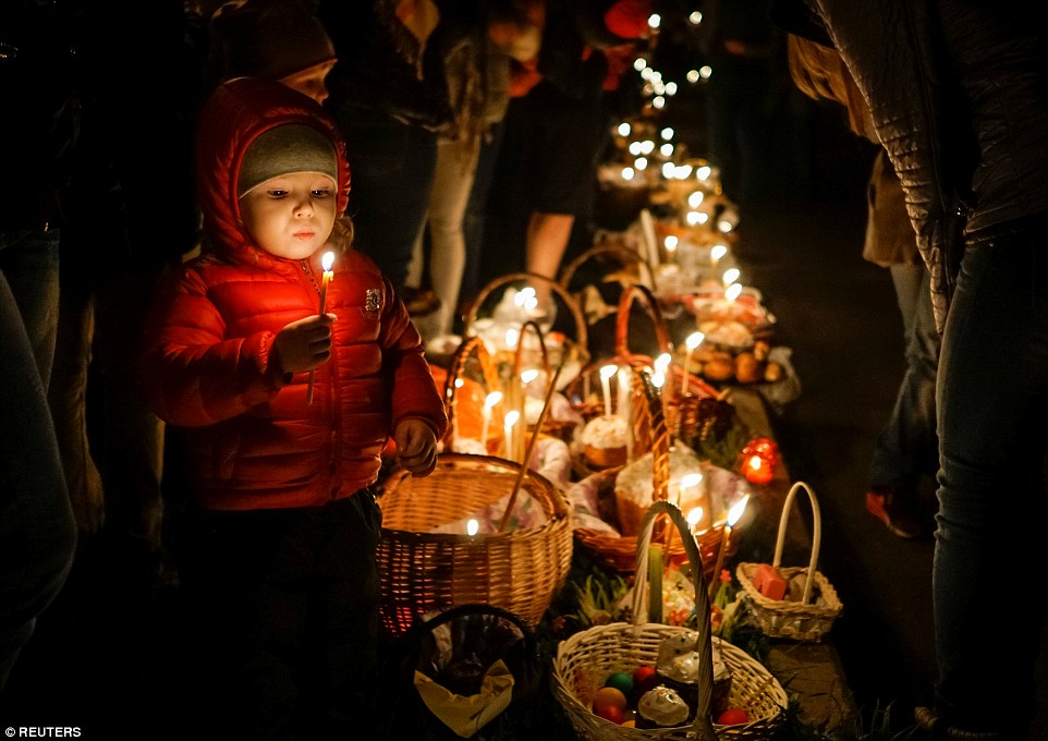 "A child holds a candle next to eggs and ""Kulich cakes"", a traditional Russian Easter bread, placed for blessing during an Orthodox Easter service in Almaty, Kazakhstan"