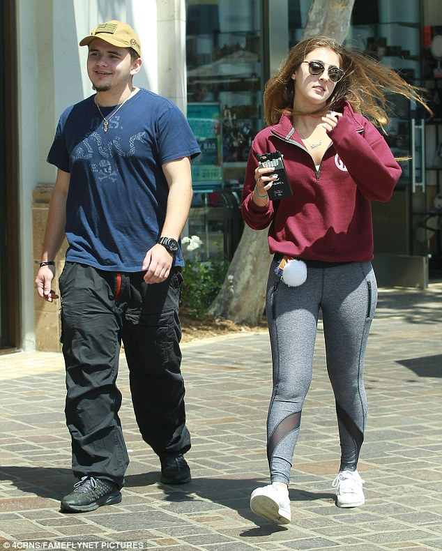 Casual date: The brunette showed off her shapely legs in yoga leggings teamed with a plum sweatshirt and white sneakers while Prince opted for a blue T-shirt, black cargo trousers and black shoes