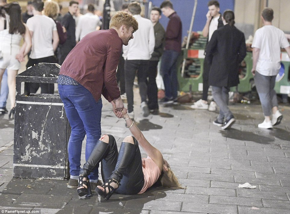 A young man helps up a woman who appears to be struggling to get back on her feet after falling over and cutting her knee in Newcastle