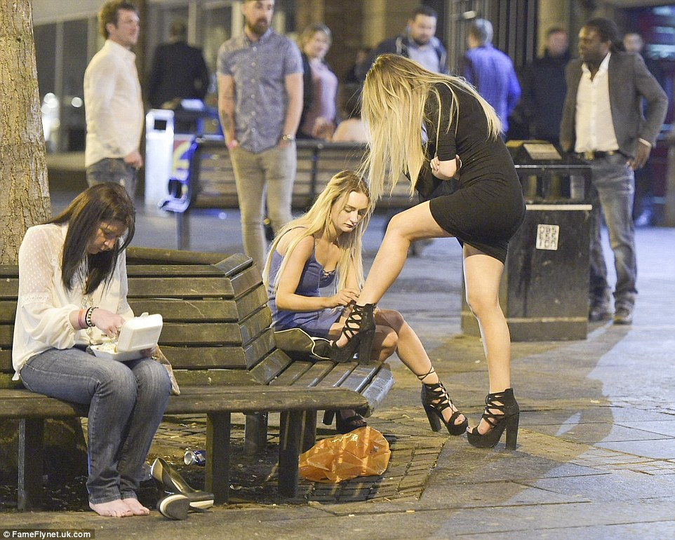 A young woman helps her friend lace up her high heels as they grab some fresh air during their night out in the northern party capital