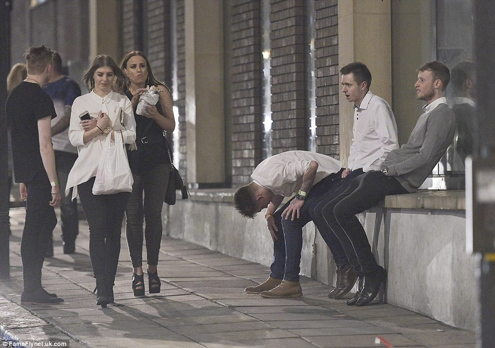One man puts his hands on his knees as two young women walk past with their takeaway kebabs following a night out in the party city