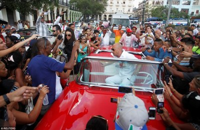 Actor Vin Diesel (center) is surrounded by fans in Cuba as he climbs out of a vintage car to attend the Chanel fashion show