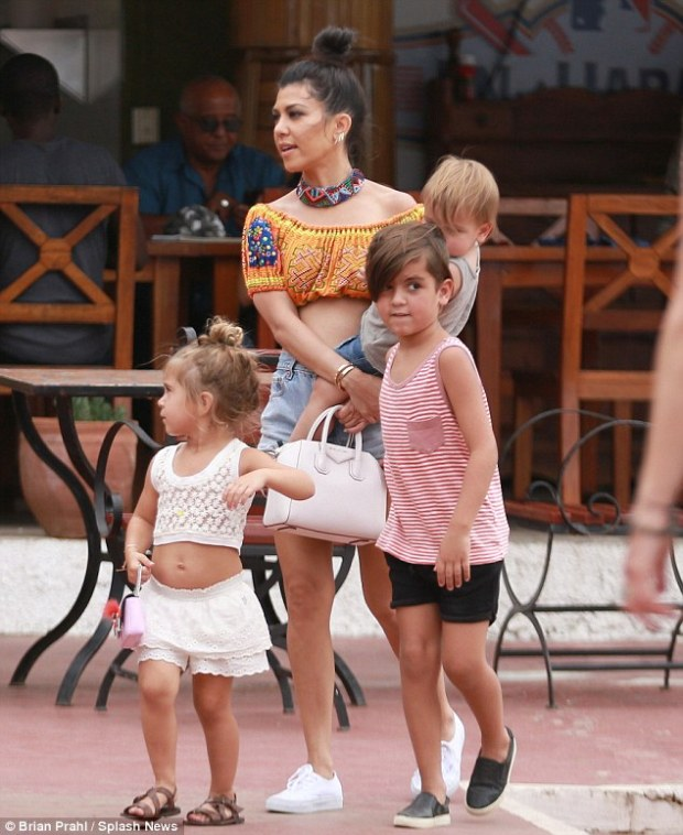 Working vacation: The 37-year-old reality star carried 16-month-old son Reign beside daughter Penelope, 3, and son Mason, 6, after touring the Havana Club Rum Museum