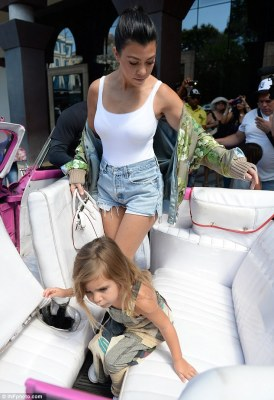 Denim darling: Kourtney teamed her bodysuit with Daisy Dukes, white plimsolls and a floral bomber jacket