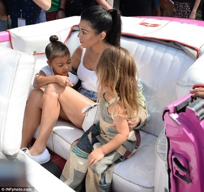 Wheel fun: Kourtney cuddled up to North and Penelope after hopping into a hot pink vintage convertible