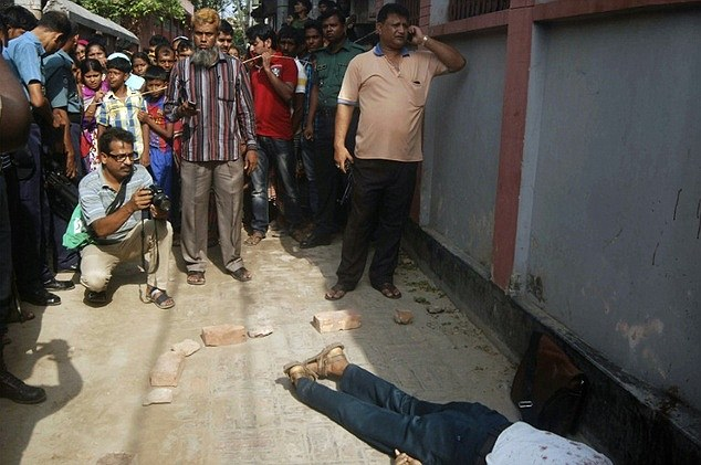People gather around the body of Bangladeshi professor Rezaul Karim Siddique after he was hacked to death on April 23