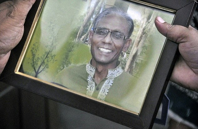 A man holds a portrait of Bangladeshi professor Rezaul Karim Siddique. Islamic State later claimed responsibility for the murder