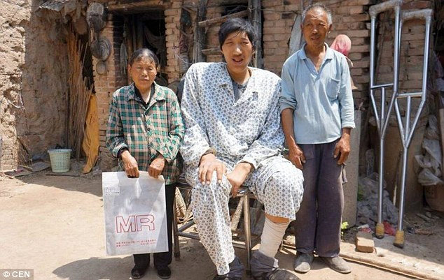 Family: The villager from rural Shandong, east China, still relies on his parents (pictured) as an accident has meant that he cannot walk without crutches