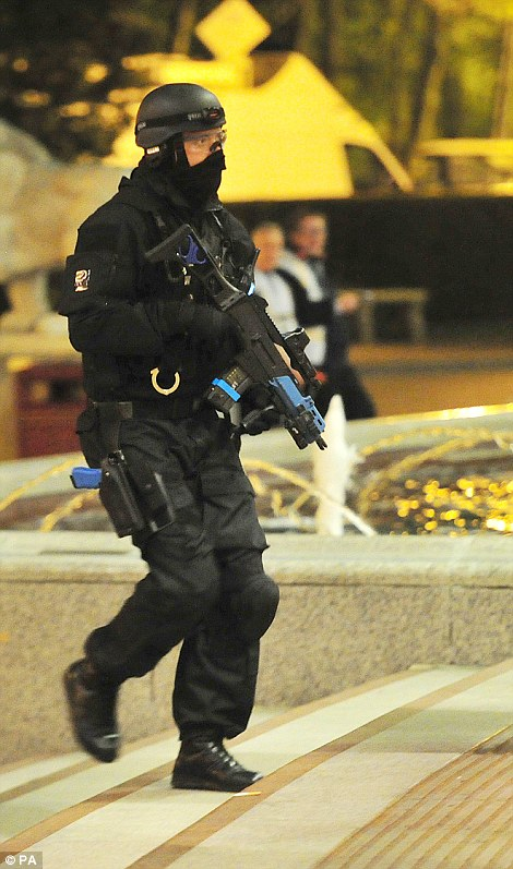 All go: An armed policeman is seen entering the shopping mall as officers attempt to gain control of the situation