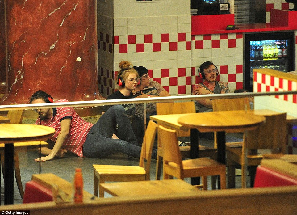 Hiding: Four 'shoppers' - some injured and others just seeking to stay away from the attackers - are pictured hiding in a burger joint