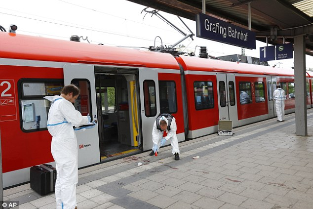 Investigators probe the crime scene where a 27-year-old man attacked four passengers at Grafing station near Munich leaving one dead and three injured