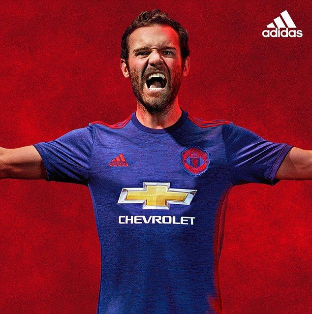 United's Spanish midfielder Juan Mata shows off the new blue away kit with red details and logos