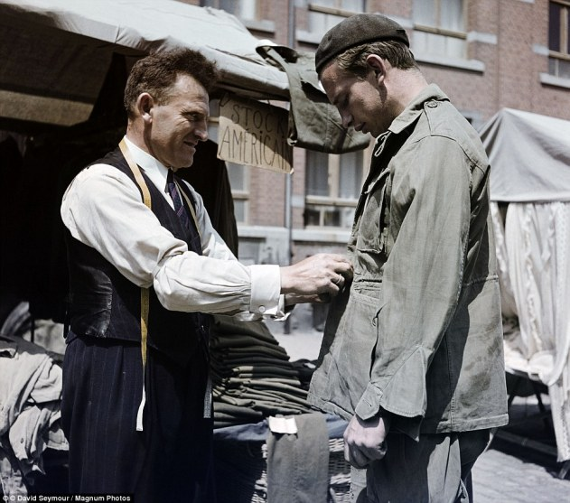 A man in Bastogne, Belgium, is fitted with discarded U.S. military clothing. The city was the centre of a brutal siege, launched as part of the German counter offensive known as the Battle of the Bulge. The siege last several days and saw at least 3,000 people killed
