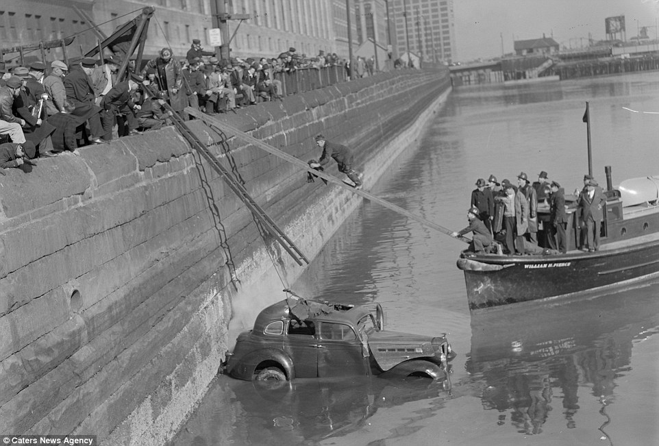 In this interesting photos members of the fire brigade and police department try to rescue people from a car stuck in Boston's Fort Point Channel