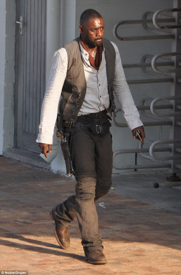 Getting into character: The 43-year-old British actor also had an ammo belt slung around his waist and a gun in a holster sitting to his side as he strolled across the South African set