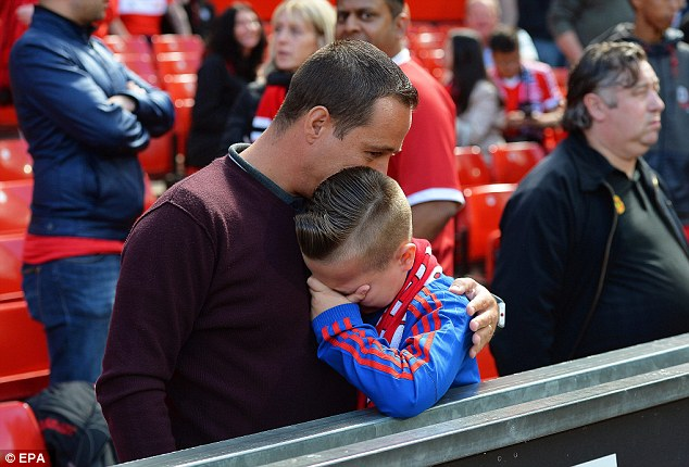 A young boy is consoled after fans were told the game would be postponed until Tuesday following news of a 'code red' security breach