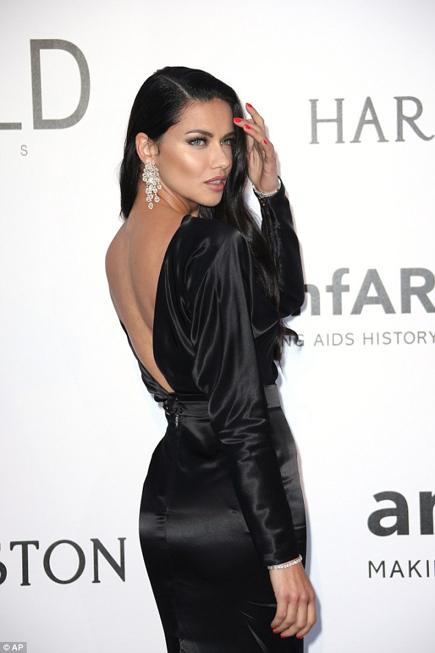 Slick:The satin gown featured a dramatically scooped back, while the tailored gown perfectly sat on her perky derriere - helping emphasise her physique