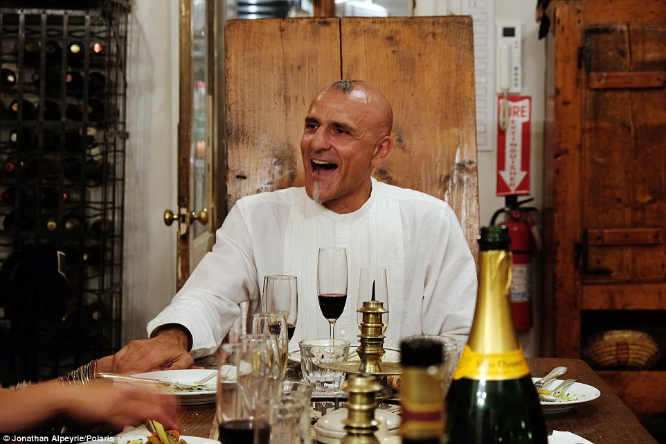 Host with the most: Michel holds the hand of a dinner guest as he enjoy a glass of red wine and food at his long table