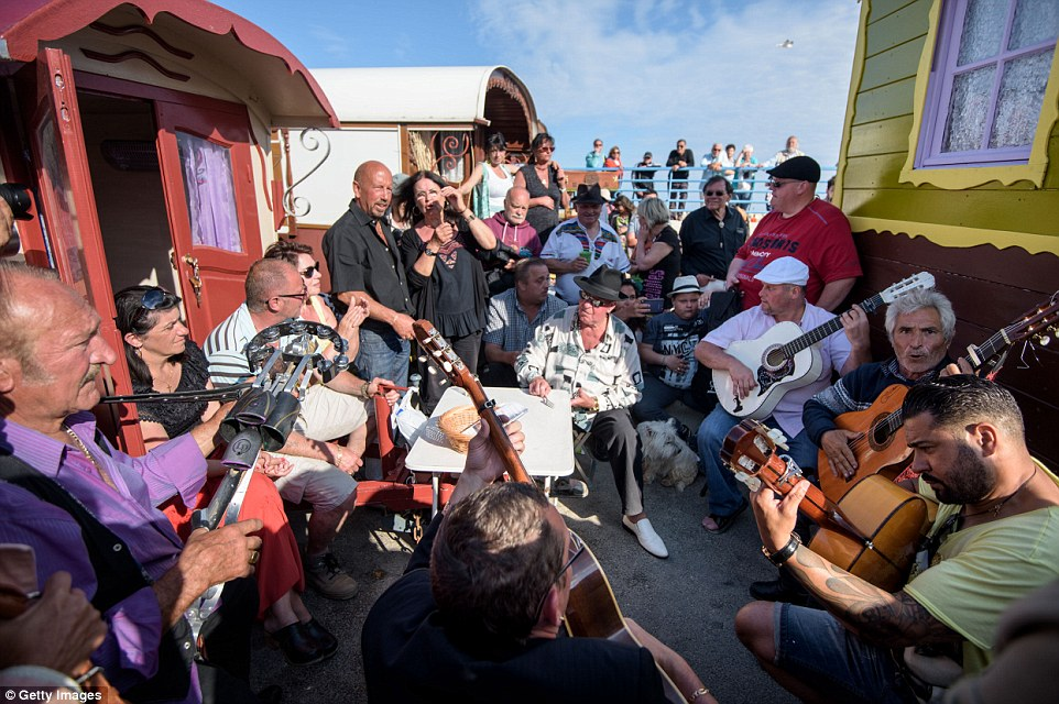 Gypsies sing and play guitar between their folklore wagons shortly before the procession to the sea with the statue of the saint
