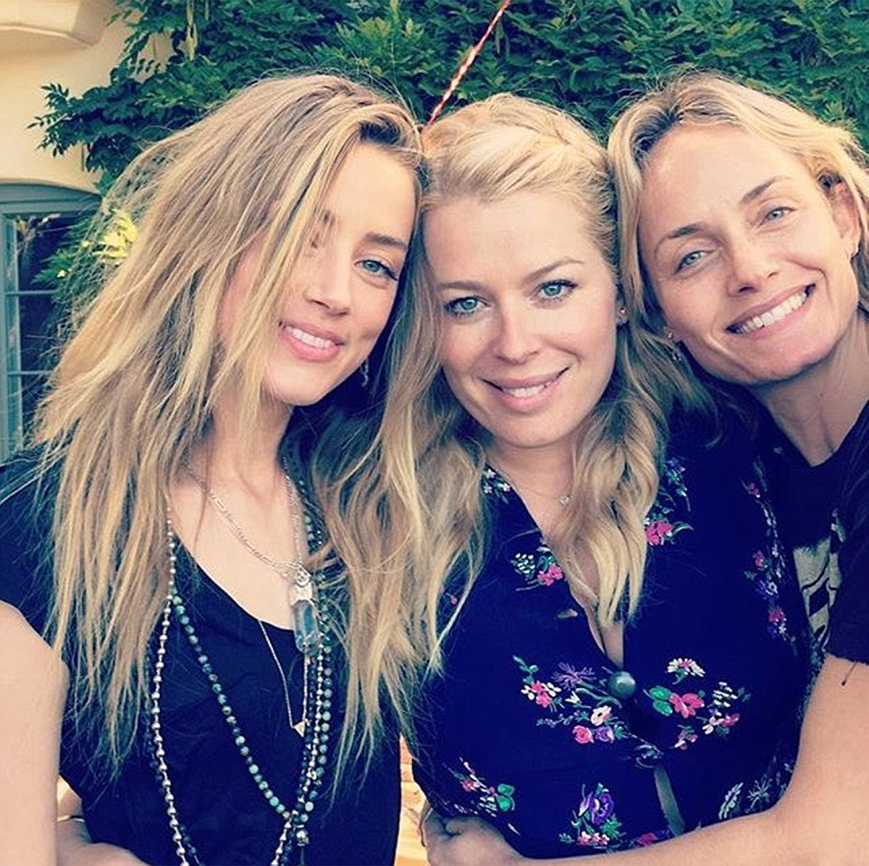 Pictured is Amber Heard (left) at her friend Amanda de Cadenet's (centre) birthday party with Amber Valletta on Sunday - the day after she was allegedly attacked. Her hair covers the areas which appeared to be bruised the day before. The picture was posted on Instagram and has since been deleted