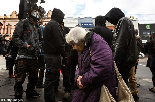 An old woman attempts to continue her daily routine as she walks past a group of protesters