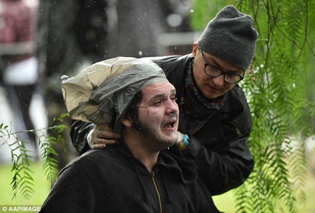 One man aids another protester while wearing gloves in a bid to avoid touching the OC spray covering the man's face