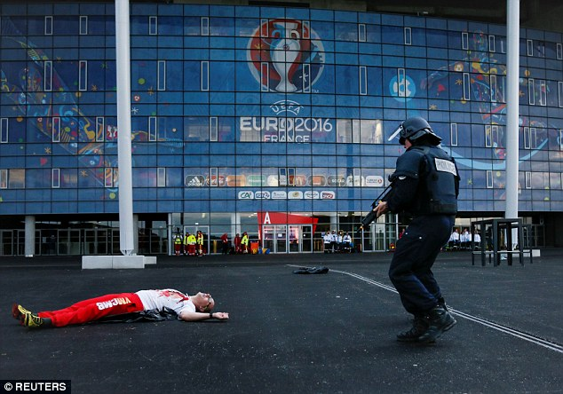 An actor covered in fake blood lies pretending to be injured outside the Stade des Lumieres as an officer carrying an assault rifle approaches