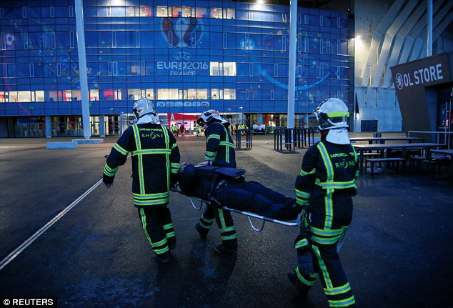 Three French firefighters stretcher a mock victim from the scene during the drill near one of the Euro stadiums