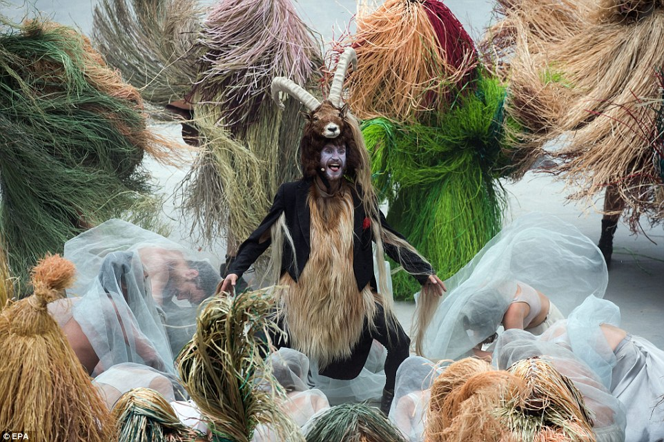 Artistic: The goat-man yells on the stage while surrounded as dancers dressed up as straw bales and surrounded by men and women in veils