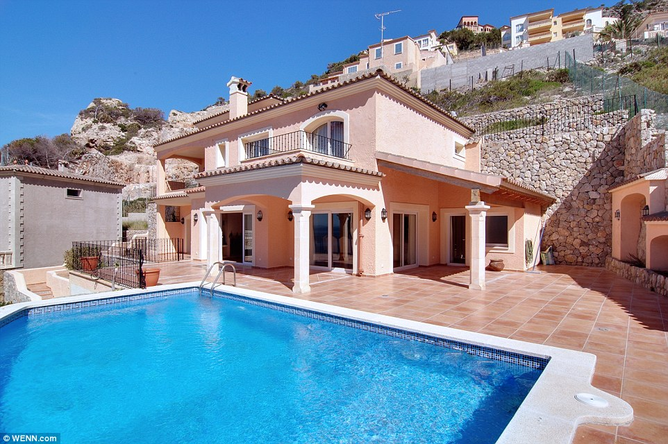 Inviting: The home's bedrooms and balcony overlook the bright blue swimming pool and Mediterranean sea