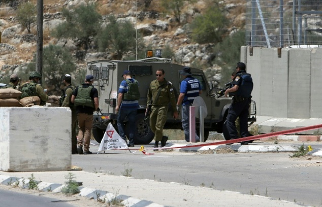 Israeli security forces inspect the scene of a stabbing attack at a checkpoint near the West Bank city of Tulkarem on June 2, 2016