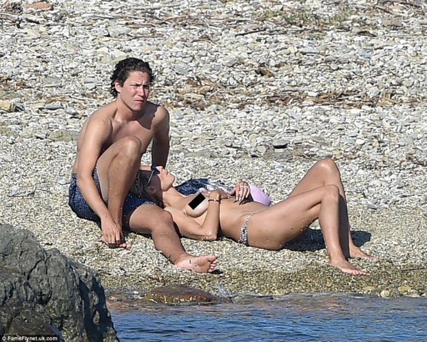 Chilling out: Heidi topped up her tan without a top on, leaning against beau Vito on the coastline