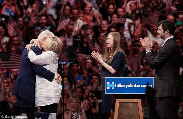 Hillary Clinton hugs her husband bill, as the couple's only daughter Chelsea and her husband Marc Mezvinsky applauds