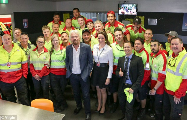 The airline's founder, pictured with other Virgin employees, said the man, who was on standby at the time, 'must have thought he was dreaming' when he woke him up