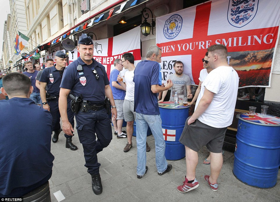 Officers from the French riot police, the CRS, patrol the centre of Marseille on Friday as England fans from Leicester and Derby drink and mingle happily over a few beers