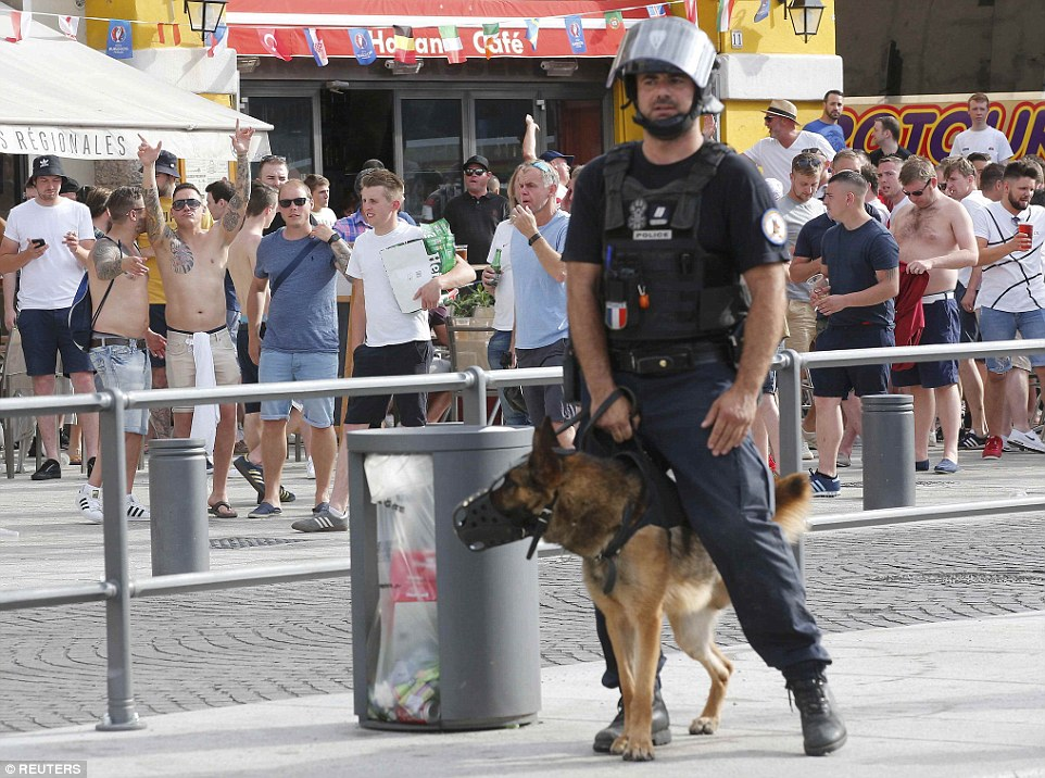An officer from the specialist dog team patrols the streets of Marseille as football fans drink and socialise outside one of the city's bars